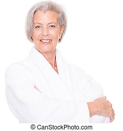 Senior woman with bathrobe in front of white background