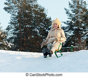 Yuong woman sliding downhill on sledge in winter