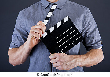 Man with movie clap over dark background