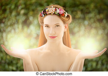 Beautiful fairy woman with glow in hands on natural green...