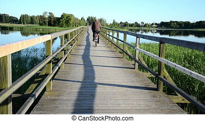 senior man bicicle bridge - grey head man drive bicicle on...