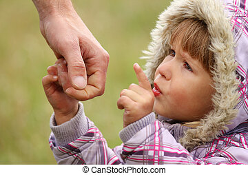 parent holds the hand of a little daughter - parent holds...