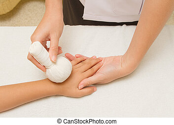 Children massage forearm with herbal compress balls