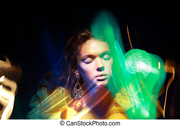 Flutter. Face of Woman in Blurry Colorful Lights....