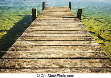 Jetty of weathered wood over a lake with blue water and...