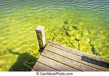 Part of a jetty over a lake of weathered wood with...