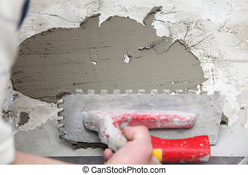 Construction worker is tiling at home tile floor adhesive -...
