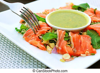 Spicy salmon salad and wasabi sauce with fork