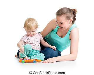 Mother and baby girl having fun with musical toy. Isolated...