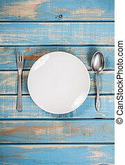 Empty white plate on weathered blue wooden table