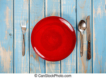 Empty red plate on blue wooden table with knife, spoon and...
