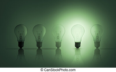 Light bulbs in a row with one lit up against green...