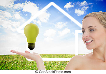 Young woman looking at green light bulb against white house