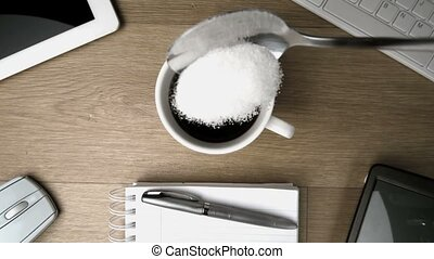 Sugar in teaspoon falling into cup of coffee on a desk in an...