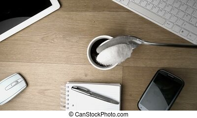 Teaspoon of sugar powder being spilled into and around a cup...