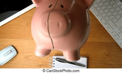 Piggy bank falling on a desk beside tablet pc and keyboard...