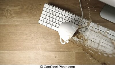Cup of tea spilled out over a white keyboard in slow motion...