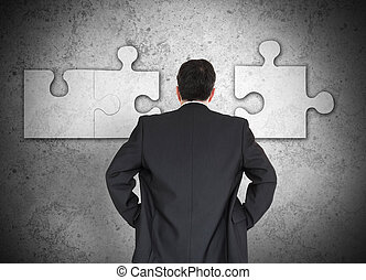 Businessman figuring out puzzle - Businessman figuring out...