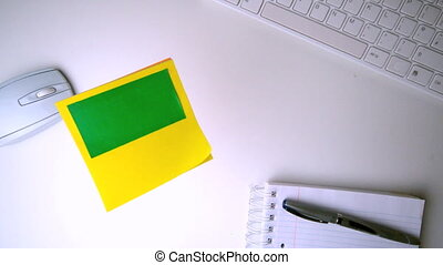 Yellow post it with chroma key falling on office desk in...