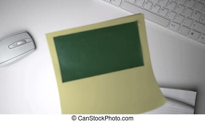 Yellow post it with green copy space falling on white office...