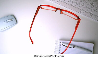 Red glasses falling onto office des