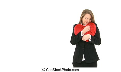 Woman cuddling heart pillow - Woman stands in front of white...