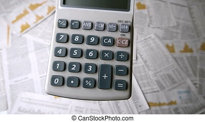 Pocket calculator falling and bouncing on papers with...