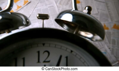 Ringing alarm clock falling over sheets of paper with...