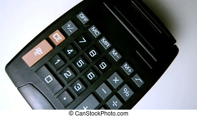 Black calculator falling on white s - Black calculator...