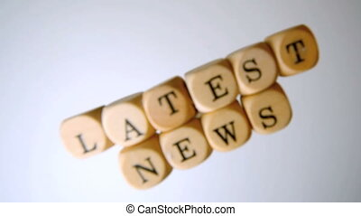Latest news spelled out in dice falling and seperating on...