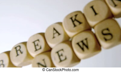 Breaking news spelled out in dice falling and seperating on...