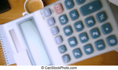 Pocket calculator falling on office desk beside coffee cup...