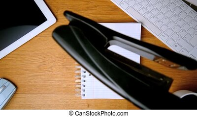 Stapler landing on notepad on office desk with tablet pc and...