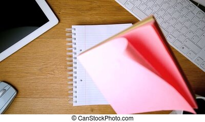 Pink post its falling on notepad on office desk with...