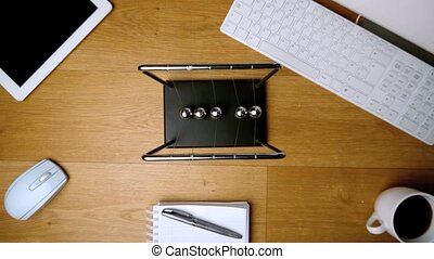 Overhead of newtons cradle toy on office desk beside...