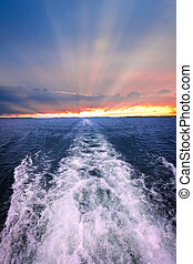 Sunset over ocean with boat wake - Wake of boat at beautiful...