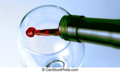 High angle shot of red wine being poured into glass in slow...