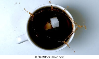 Sugar cubes falling in cup of coffee in slow motion