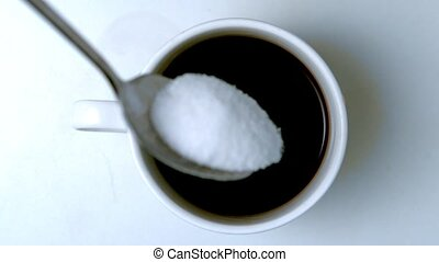 Teaspoon pouring sugar into cup of coffee in slow motion