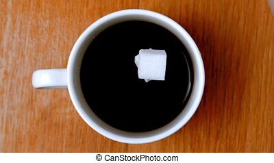 Sugar cubes falliing into coffee cup in slow motion