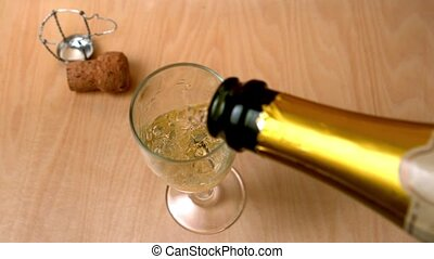 High angle view of champagne being poured into flute in slow...