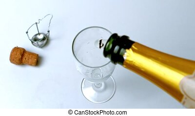 Champagne being poured into flute on white surface in slow...