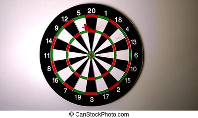 Dart hitting the dart board beside another dart in slow...