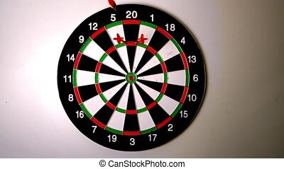 Dart hitting the dart board between two other darts in slow...