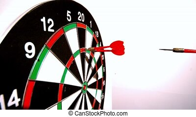 Dart hitting the dart board between two other darts side...