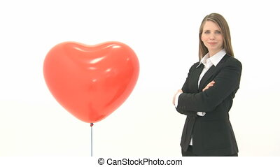 Woman standing next to heart balloon and crosses her arms