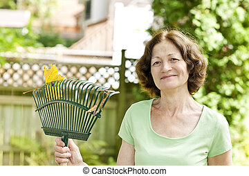 Senior woman holding rake