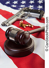Gun laws - A wooden gavel on an american flag with a gun and...