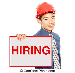 We Are Hiring - A man holding a job hiring signboard or...