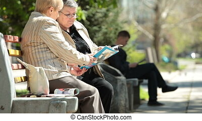 Senior Citizens - Senior women friends reading magazines in...